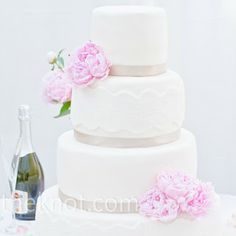 Simple white wedding cake with lace and ribbon