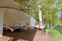 Terrasse ensoleillé de cette tente suspendue aux chaises longues et petite table d'appoint