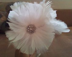 """Just made one of these DIY feather flowers. I found that they looked prettier without trimming the edges. Also, I added pearls in the middle instead of the jewel bead or whatever that thing is. Hot glued it to a 10""""x12"""" glass picture frame which will hold a picture of Drew and I at our reception. Got a lot of feathers, trying a bunch of different options. <3 -Ashleigh"""