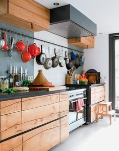 a long metal bar that stretches from end to end of kitchen wall and holds all their pots, pans, and cooking utensils.    The bar blends in seamlessly with the rest of the rustic/industrial kitchen decor, which includes wooden cabinets constructed from a single elm tree.. Original pinner asks: Wonder what they use to hang the stuff??