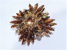 ITEM # 121659  Beautiful verified DeLizza & Elster aka Juliana amber topaz rhinestone brooch / pendant. Brooch has a pendant on the back as well.   Top row of the brooch consists of a large round amber faceted glass rhinestone with 12 small amber faceted glass accent rhinestones surrounding it. Same row consists of 4 medium topaz round faceted glass rhinestones and 12 long spiky topaz faceted glass navettes. Bottom row consists of 16 same long spiky topaz faceted glass navettes and 8...