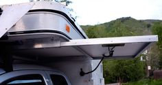 Kodachrome built a slide-out solar panel rack under the cabover of his ATC Bobcat, and it's lockable.