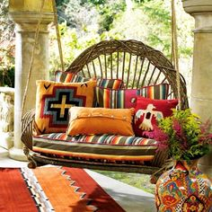 Garden Swing in Grecian column patio.  The contrast of warm, vibrant southwestern patterns in the pillows & rug are amazing!