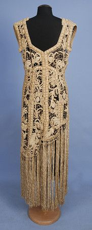 RIBBON EMBROIDERED LACE OVER-DRESS, c. 1920. Sleeveless ivory net decorated with heavy padded silk embroidery and French knots to below the hip, having a skirt of long ribbon fringe, back closure. Back