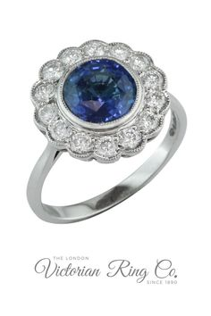This sapphire engagement ring features a two carat blue sapphire surrounded by a halo of round diamonds. The platinum cluster ring is made in an Edwardian style. Order online or visit us in Hatton Garden by appointment. #Sapphire #EngagementRing #PlatinumRing #HattonGarden #ClusterRing #BlueSapphire #LondonVictorianRingCo #LVR