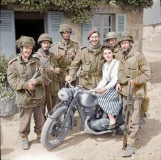 "Glider troops of ""D"" Company, 2nd Battalion The Oxfordshire and Buckinghamshire Light Infantry, who had been on their way to DZ-W on the 8th or 9th June 1944 to collect supplies, pose for a photograph around a German DKW NZ 350 motorbike in Bénouville, Calvados with a local French girl."
