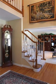 Casual 2-story entry with oak flooring & painted railing staircase.