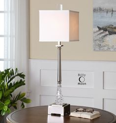 Polished nickel plated lamp metal with glass accents and a crystal finial. The square hardback shade is a silken white linen fabric.  http://www.decorbound.com/store/#!/Venarotta/p/38792732/category=10279031