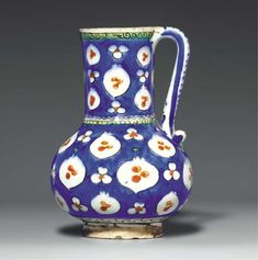AN IZNIK POTTERY JUG  OTTOMAN TURKEY, CIRCA 1560  Of baluster form on short foot rising to slightly flaring mouth and with simple loop handle, painted under the clear glaze in cobalt-blue, bole-red and black heightened with green with white stylized pomegranates and cintamani reserved against a blue ground, white plaited register with green cusped fringe at waist, spirals on green border at rim, intact with   8in. (20.4cm.) high