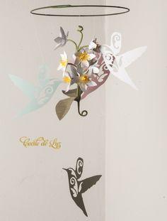 Móbile de papel imitando os beija flores na natureza. Esta simulação nos traz a consciência do quanto a natureza é perfeita e imprescindível em nossas vidas.    - Medidas: 22 de diâmetro x 48 comprimento  - Feito em papéis importados, 180 gramas  - Opção de cor das flores: tons de amarelo, tons de rosa, tons de lilás  - Opção de cor dos beija flores: branco, preto, rosa, lilás,amarelo, azul R$ 110,00