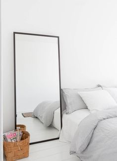 natural fresh bed linen in a light gray hue | mirror next to the bed and basket for books & mags
