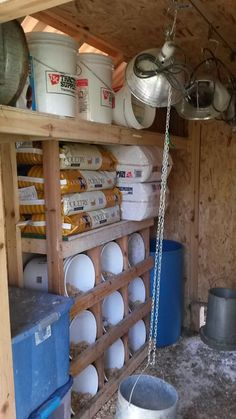 Nesting area of our hay wagon chicken tractor chicken coop. We use 5 gallon buckets to provide nesting boxes which are well sized and easy to clean. Each bucket can be removed and throughly cleaned and sanitized when necessary. Having shelves above the nesting boxes provides for easy and close storage for extra feed and bedding materials. The lower left shows the top of our dust bathing bucket constructed from a plastic tote and filled with sand it provides a great place for the chickens…