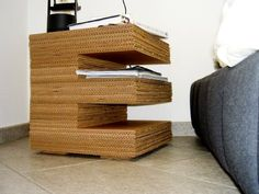 """genius table, made of corrugated cardboard. it can be made in any letter, but the """"E"""" conveniently adds extra shelves on the side."""
