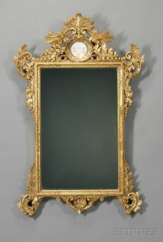Sevres Porcelain-mounted Carved Giltwood Mirror, the crest with scrolling acanthus leaves centering an oval reserve inset with porcelain plaque with two putti flanking the factory's mark, over stiles with further protruding acanthus leaves and pendant carved shell, with Sevres mark,.