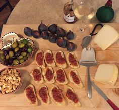 Bruschetta, olives, fresh figs, cashews, and 2 kinds of Pecorino on a wooden…