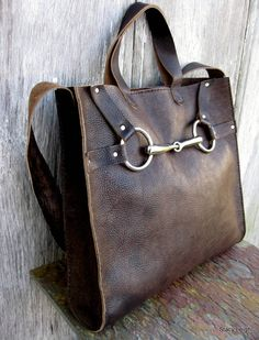 Equestrian Horse Bit Tote Bag in Rugged Distressed Brown Leather by Stacy Leigh One of a kind leather tote bag with a genuine horse bit on the front. Ive used a new silver bit on this bag. This leather is a chocolate brown with lots of character and darker spots and variation throughout. The leather has a very rugged, and aged look. Unlined, with two drop in pockets. Two short handles and one 32 shoulder strap so you may use as a tote or put it on your shoulder. The bag is 13 across by 12.5…