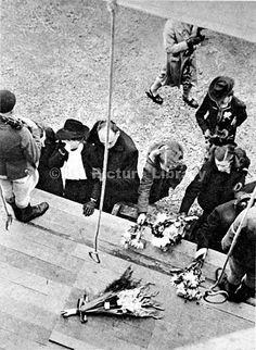 Civilians laying flowers on the gallows at Breendonck fort, Belgium, 1944. This fort, situated between Brussels and Antwerp, was used by Nazi security services during their occupation of Belgium between 1940-44. As such, it was the scene of many Nazi atrocities; the gallows shown had a long drop, designed to slowly strangle victims to death.
