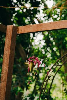 Delicate floral decor hanging from a wooden arch | Image by Hannah Costello