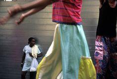 Alex Webb  CUBA. Havana. 2002. Havana Vieja. Procession of stiltwalkers.