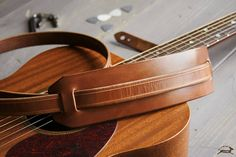This handmade leather guitar strap is cut from beautiful full-grain leather. The two-piece folk design has keyholes notched into both ends for a wide adjustment range. The main strip is 1 thick, and It has a movable shoulder pad for added comfort. This strap is compatible with most