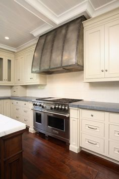 Large kitchen with barrel range hood with forged iron straps, ivory kitchen cabinets with concrete countertops, subway tiles backsplash, coffee stained kitchen island with marble countertop and beadboard coffered ceiling.