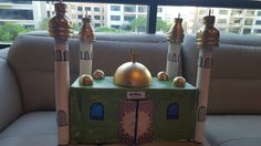A mosque we designed and created out of recycled household material. (We used Aab-e-Zam zam carton to maintain the sanctity of the mosque). We avoided shoe cartons and toilet rolls, instead used cardboard roles that come from Wrapping papers. kitchen rolls can be used. the domes are made with water bottles cut half way up, the central dome was made by cutting in half a plastic ball n painting over it. My 6 year old son created it while i gave design guidance and window cutting. Ramadan Activities, Origami Mobile, Cardboard Design, Bottle Cutting, Wrapping Papers, Toilet Paper Roll Crafts, Ramadan Decorations, Dramatic Play, Diy Arts And Crafts