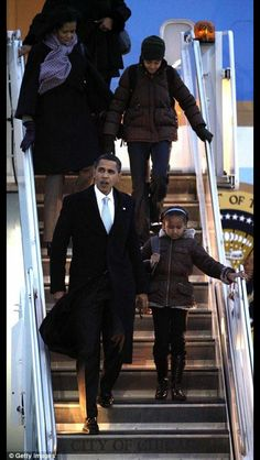 44th President of the United States BarackObama and First Lady Michelle Obama descend the steps of Air Force One with daughters Malia and Sasha.
