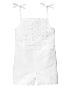 Our lovely poplin romper is embellished with pretty floral eyelet cut-out details and button accents in front and around the scalloped cuff. Finished with darling tie straps and front pockets. Elasticized back waist creates a stylish shape. Full cotton batiste lining for exceptional comfort.