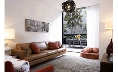 Living room with brown lether couches decorated with red decorative pillows-Home and Garden Design Ideas