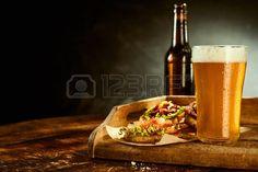 Vaso alto lleno de cerveza y una botella junto a las tapas envueltas en papel sobre la mesa de madera