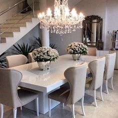Sleek white table with ivory/beige dining chairs, top off the sophisticated look with a gorgeous chandelier...I love this!