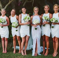 White bridesmaids in short gowns with nude heels. Love the high necks and tulip resembled bottoms.