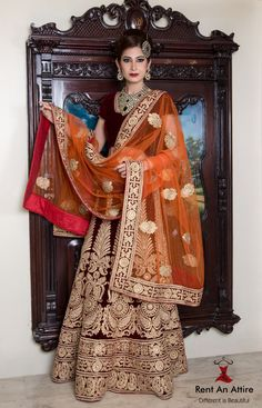 Maroon bridal lehenga adorning exquisite embroidery coupled with a sassy velvet texture. It is teamed with an orange net dupatta that contrasts with the lehenga to perfection. Our wedding collection of beautifully crafted bridal lehengas, gowns, groom's sherwanis & many more just in at the store! Visit Rent an Attire to explore the all new collection! #Bridalwear #Groomwear #Designerwear #Royal #Lehenga #Gold #Embroidery #IndianFashion #RentAnAttire