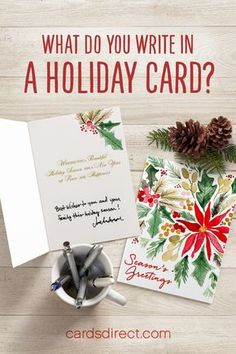 """An open and closed version of a floral holiday greeting card is lain against a woodgrain table. Other objects like a mug full of pens, pine cones, and pine needles add subtle seasonal accents, with the words 'What do you write in a holiday card?"""" written above the items in red. Cardsdirect.com - the company name - is written below the arrangement in red."""