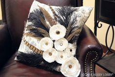 Posh up a standard accent pillow with a bold-as-can-be cluster of guinea fowl and ostrich feathers, using hot glue to secure. Then, top off the design with satin flowers and coordinating buttons. Voilà!