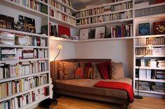coin lecture avec bibliothèque en bois, canapé d'angle en marron et sol en…