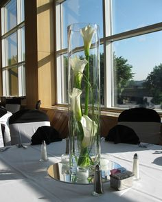 Calla lilies and bear grass inside a cylinder vase. Looks very elegant! Love the composition of the callas and the grass really adds to it..
