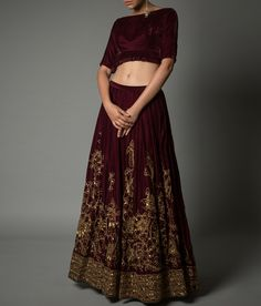 A resplendent velvet lehenga in a deep wine colour embellished with gold pita embroidery and stone work. The lehenga comes with a matching cropped choli.