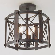"A simple design with masculine touches, this ceiling light features classic styling with natural materials. The wood beams surrounding the frame are finished in a medium dark stain which complements the rough texture of the Black finish. Damp location rated. 6"" canopy. 5.5 lbs. (14.5""Hx15""W). 3x60 watts max candelabra base sockets."