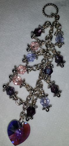 Pretty in Purple. I made this cell charm in purples with pink accent Swarovski crystals. The Swarovski purple heart is offset by the multiple shades of purple and pink that makes it sparkle! It is $15.