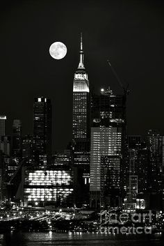 Blue Moon over Manhattan.  A black and white view of the Blue Moon of July 2015 rising over the Empire State Building and New York Skyline with the Hudson River in the foreground.
