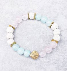 《《 OIL DIFFUSER COLLECTION 》》   ~~THE DETAILS~~  This handmade Aromatherapy Essential Oil Diffuser Bracelet is designed with White Lava Stone, Pink Quartz  Aqua Blue Quartz Gemstones, and Gold Wavy Spacers; finished with an exquisitely detailed Gold Shell!  The perfect bracelet for Ocean  Beach Gemstone Bracelets, Bracelets For Men, Aromatherapy Jewelry, Shell Bracelet, Birthstone Charms, Pink Quartz, Oil Diffuser, Gift For Lover, Stone Beads