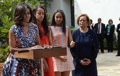 First Lady Michelle Obama was accompanied by her two daughters Malia (2L) and Sasha (2R) and her mother Marian Robinson (R) to speak during a ceremony at public library Ruben Martinez Villena during a historic trip to Havana, Cuba on March 22, 2016.
