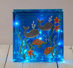 Lighted glass block with hand painted underwater scene with whales and turtles. The block was tinted a turquoise blue, hand painted with an