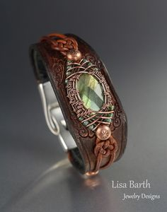 Hand woven copper bezel around a really shiny Labradorite cab.  The leather is hand cut, tooled and dyed to go with the centerpiece.  :)