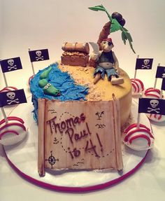 Pirate cake with pirate theme cake pops. Buttercream with gum paste accents. All accents and figures hand made from gum paste. By Angie Bakes Cakes