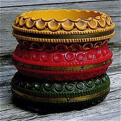 ...intensely carved Bakelite bracelets banded in brass trim...