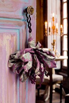 Un pompon servant de bijou de porte, en toile de jouy pliée et collée