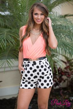 It doesn't get any better than this polka dot romper! It has black and white polka dot shorts with a neon coral top with a black belt, open back, and lining under the shorts! Add wedges for the perfect summer look!