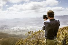 Travel and technology concept on a hiker man taking tablet photo from a Western Tasmania mountain peak. Captured on Mount Zeehan, Australia by Jorgo Photography - Wall Art Gallery